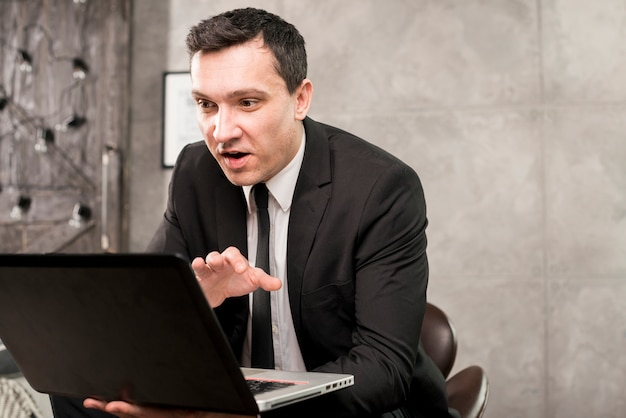 Young surprised businessman browsing laptop at home