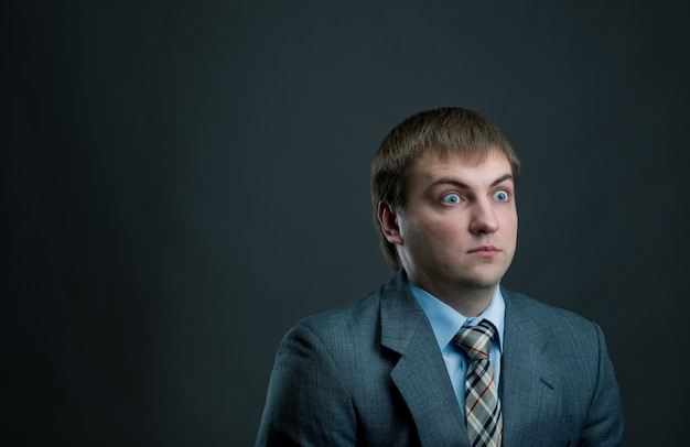 若い驚きのビジネスマンのスーツと黒の背景にネクタイ。思いやりのある実業家、男性マネージャーはショックを受けた