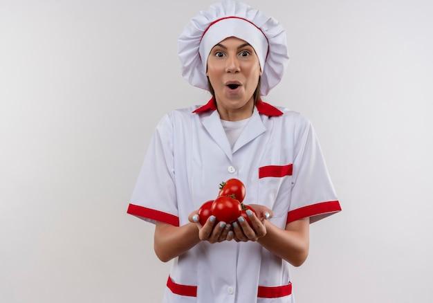 La giovane ragazza caucasica sorpresa del cuoco in uniforme del cuoco unico tiene i pomodori nelle mani su bianco con lo spazio della copia