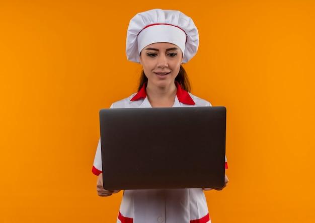 Молодая удивленная кавказская девушка-повар в униформе шеф-повара держит и смотрит на ноутбук, изолированный на оранжевой стене с копией пространства