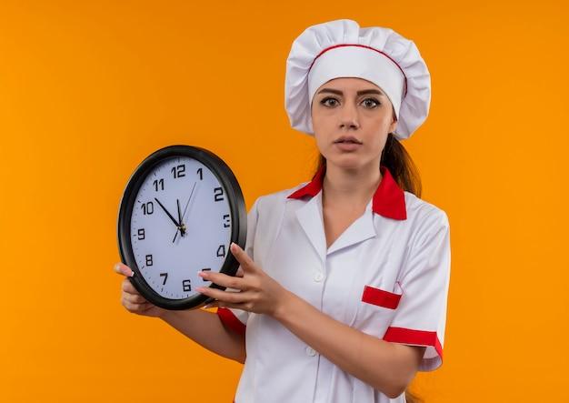 シェフの制服を着た若い驚きの白人料理人の女の子は、コピースペースでオレンジ色の壁に分離された時計を保持します
