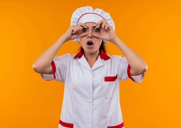 요리사 제복을 입은 젊은 놀란 백인 요리사 소녀 복사 공간 오렌지 벽에 고립 된 손가락으로 눈을 뜨고