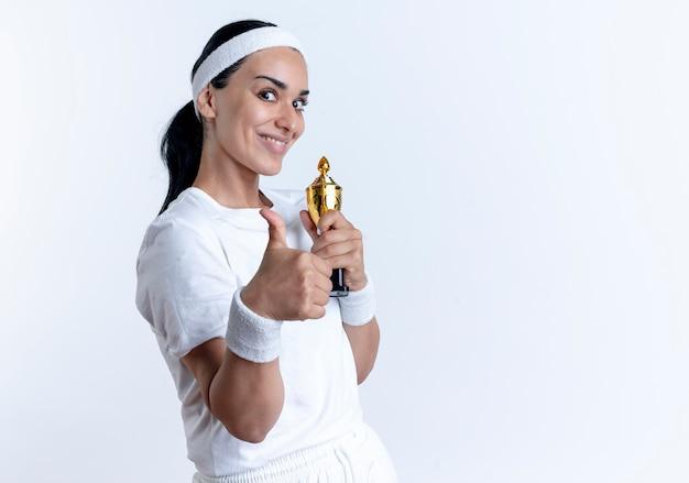 머리띠와 팔찌를 착용하는 젊은 놀란 백인 스포티 한 여자는 우승자 컵을 보유하고 복사 공간이있는 공백에 고립 된 엄지 손가락