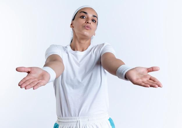 Молодая удивленная кавказская спортивная женщина с повязкой на голову и браслетами указывает вперед руками, изолированными на белом пространстве с копией пространства