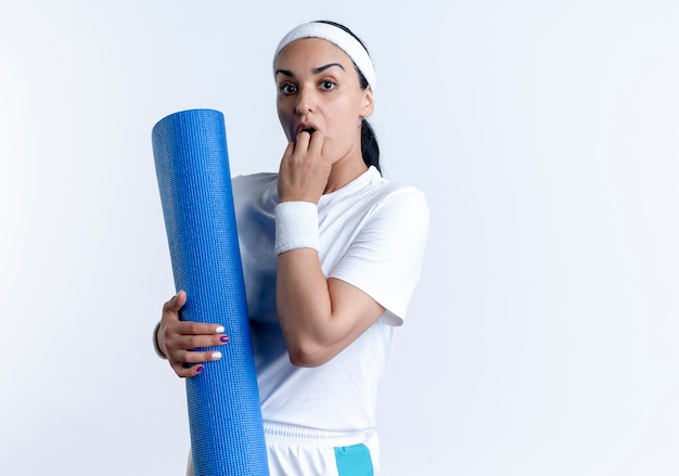 Giovane donna sportiva indoeuropea sorpresa che indossa braccialetti mette la mano sulla bocca tenendo il tappetino sportivo