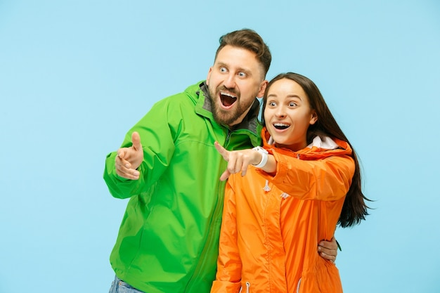 La giovane coppia sorpresa che punta a sinistra e posa in studio in giacche autunnali isolate sull'azzurro.