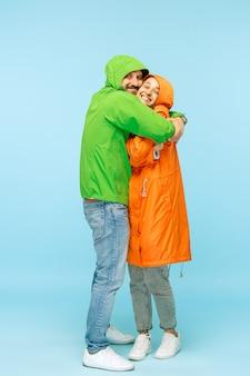 La giovane coppia sorpresa in studio in giacche autunnali isolate sull'azzurro. emozioni positive umane felici. concetto del freddo. concetti di moda femminile e maschile