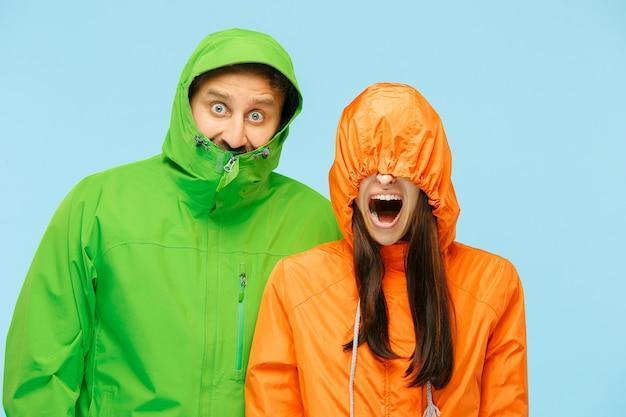 La giovane coppia sorpresa in studio in giacche autunnali isolate sul blu.