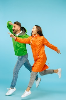The young surprised couple at studio in autumn jackets isolated on blue.