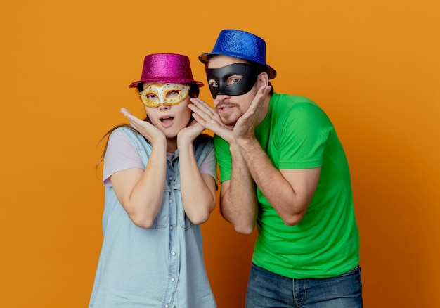 Young surprised couple wearing pink and blue hats put on masquerade eye masks putting hands on chin isolated on orange wall