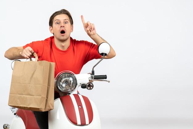 Ragazzo giovane corriere sorpreso in uniforme rossa che si siede sul motorino che tiene il sacchetto di carta e rivolto verso l'alto sulla parete gialla