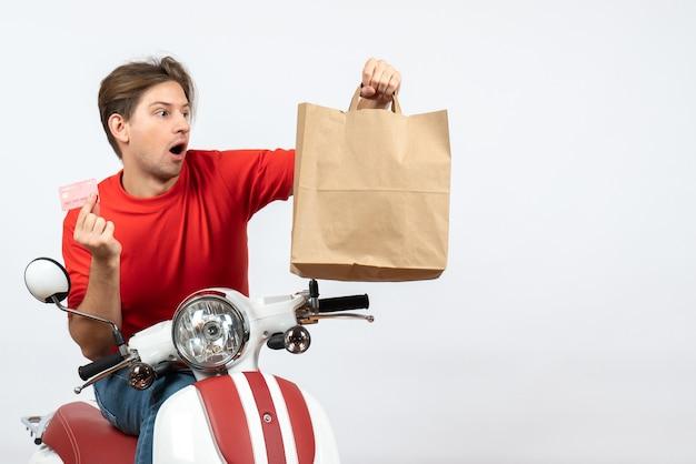 노란색 벽에 종이 가방을 들고 스쿠터에 앉아 빨간 제복을 입은 젊은 놀란 택배 남자
