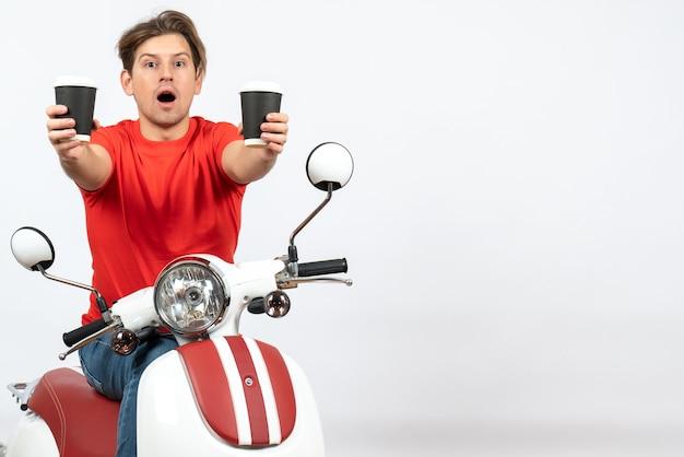 Giovane uomo sorpreso del corriere in uniforme rossa che si siede sul motorino che dà i bicchieri di carta sulla parete gialla