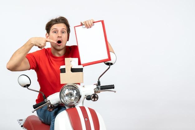 Giovane uomo sorpreso del corriere in uniforme rossa che si siede sul motorino che tiene ordini e documenti sulla parete gialla