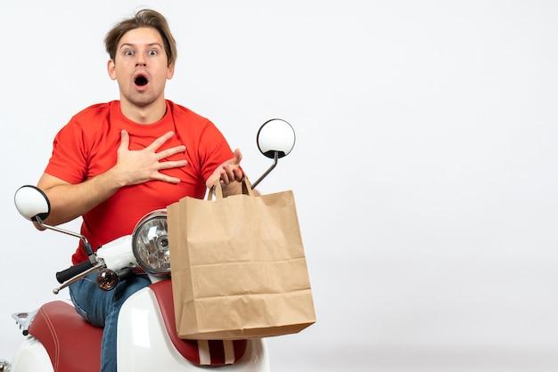 Giovane uomo sorpreso del corriere in uniforme rossa che si siede sul motorino che tiene il sacchetto di carta sulla parete gialla