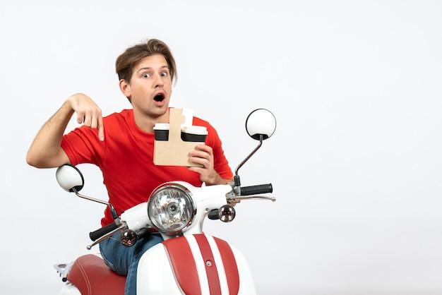 Giovane uomo sorpreso del corriere in uniforme rossa che si siede sul motorino che tiene il bicchiere di carta rivolto verso il basso sulla parete gialla