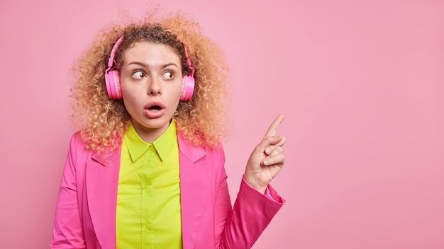 La giovane donna europea dai capelli ricci sorpresa ascolta musica tramite le cuffie tiene la bocca aperta dalla meraviglia indica nell'angolo in alto a destra indossa abiti formali isolati sul muro rosa