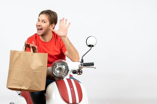 紙袋を保持し、白い壁に5を示すスクーターに座っている赤い制服を着た若い驚いた配達人