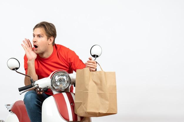 Giovane ragazzo di consegna sorpreso in uniforme rossa che si siede sul motorino che tiene il sacchetto di carta guardando da qualche parte sul muro bianco