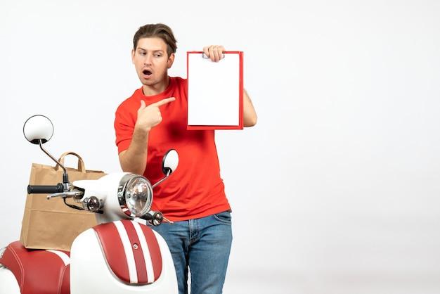 Giovane ragazzo di consegna sorpreso in uniforme rossa che sta vicino al documento di puntamento del motorino sulla parete bianca