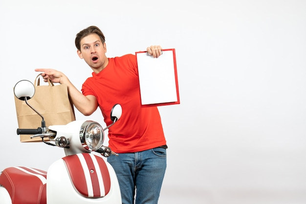 Young surprised delivery guy in red uniform standing near scooter showing document holding order on white wall