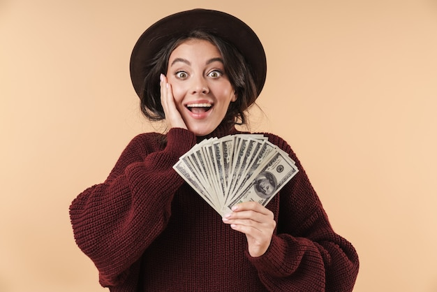 Молодая удивленная эмоциональная брюнетка женщина изолирована над бежевой стеной, держащей деньги.