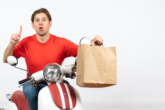 Giovane ragazzo emotivo sorpreso del corriere in uniforme rossa che si siede sul motorino che dà il sacchetto di carta rivolto verso l'alto sul muro bianco