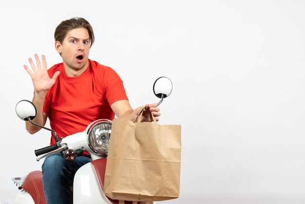 Young surprised emotional courier guy in red uniform sitting on scooter giving paper bag showing five on white wall