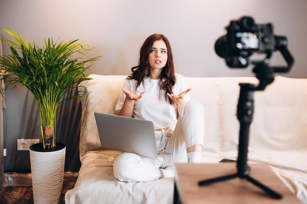 若い驚いた女性ブロガーがソファに座って、ラップトップで彼女のスピーチvlogを聴衆に録音しています。屋内でブログを書く。