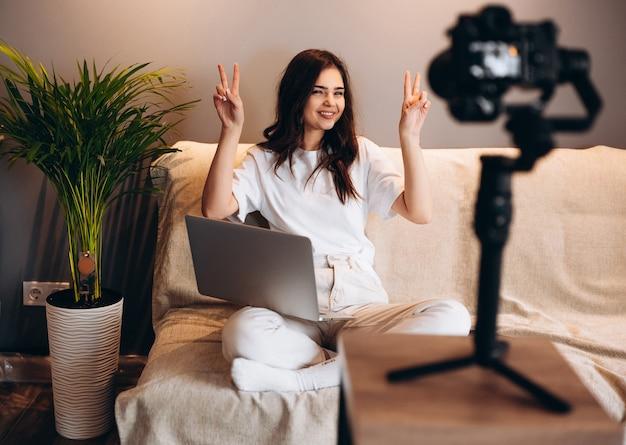 若い驚いた女性ブロガーがソファに座って、ラップトップで彼女のスピーチvlogを聴衆に録音しています。屋内でストリーミングしながら楽しんでいる幸せなインフルエンサー。