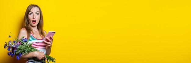 黄色の背景に携帯電話と野生の花の花束を持って驚いた若い女の子。バナー。