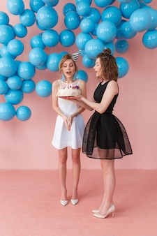 Young surprised girl holding a birthday cake and her friend standing close.