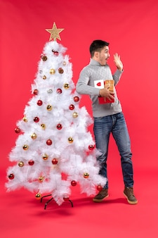 Молодой удивленный красивый взрослый стоит возле украшенной белой рождественской елки и держит свои подарки