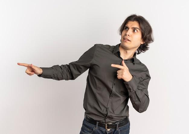 Молодой удивленный красивый кавказский мужчина смотрит и указывает в сторону, изолированную на белом фоне с копией пространства