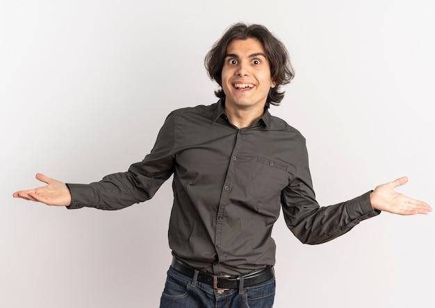Il giovane uomo caucasico bello sorpreso esamina la macchina fotografica con le braccia aperte isolate su fondo bianco con lo spazio della copia