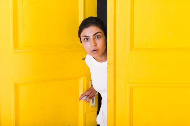 Young surprised indian woman peeking through yellow opened door