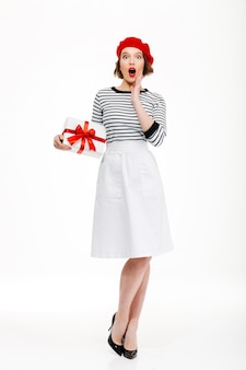 Young surprised lady holding gift surprise box.