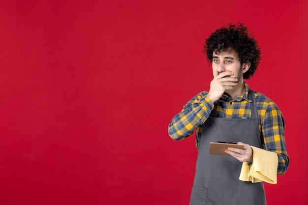 Giovane server maschio sorpreso con capelli ricci che tiene l'asciugamano prendendo ordine su sfondo rosso isolato