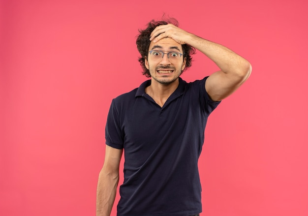 Young surprised man in black shirt with optical glasses holds head and looks isolated on pink wall