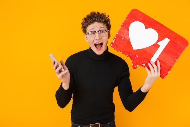 플래카드를 들고 노란색으로 격리된 휴대폰을 사용하는 안경을 쓴 젊은 놀란 남자
