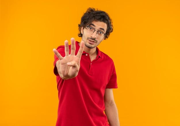 オレンジ色の壁に分離された光学メガネジェスチャー4手サインと赤いシャツの若い驚いた男