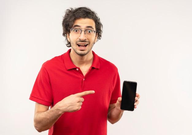 光学メガネと赤いシャツを着た若い驚きの男は、白い壁に隔離された電話を保持し、ポイントします