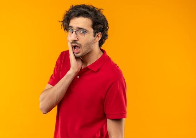 光学メガネと赤いシャツを着た若い驚きの男は顔に手を置き、オレンジ色の壁に孤立して見える