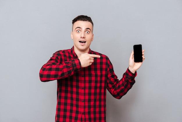 Молодой удивленный человек в рубашке показывает пустой экран смартфона и указывая на него. изолированный серый фон
