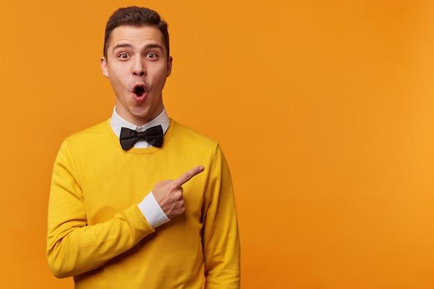 白いシャツと黒い蝶ネクタイの上に黄色いセーターを着て、指で右を向いて、wowを叫んでいる若い驚きの男