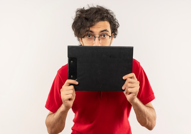 Young surprised man in red shirt with optical glasses holds clipboard and looks isolated on white wall