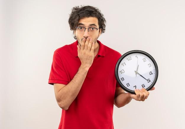 Il giovane uomo sorpreso in camicia rossa con i vetri ottici tiene l'orologio e mette la mano sulla bocca isolata sulla parete bianca