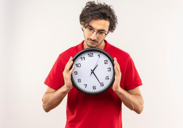 Il giovane uomo sorpreso in camicia rossa con vetri ottici tiene e guarda l'orologio isolato sulla parete bianca