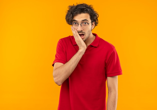 Young surprised man in red shirt with optical glasses puts hand on chin and looks isolated on orange wall