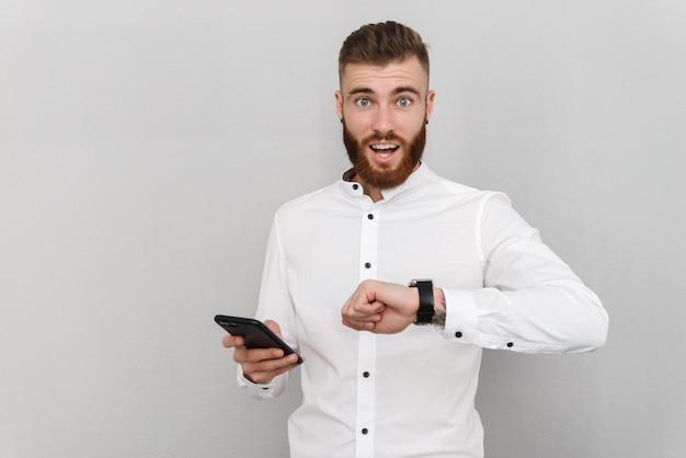 회색 벽에 격리된 스마트워치와 휴대폰을 사용하는 놀란 청년